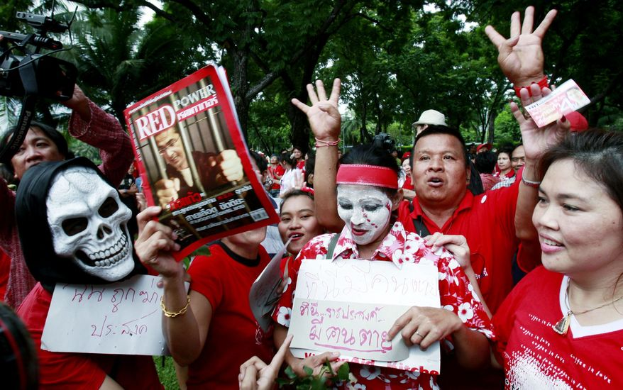 IN THEIR FACE: Red Shirt protesters are demanding a vote as a way to unseat Prime Minister Abhisit Vejjajiva, but two corruption cases could do the work for them. (Associated Press)