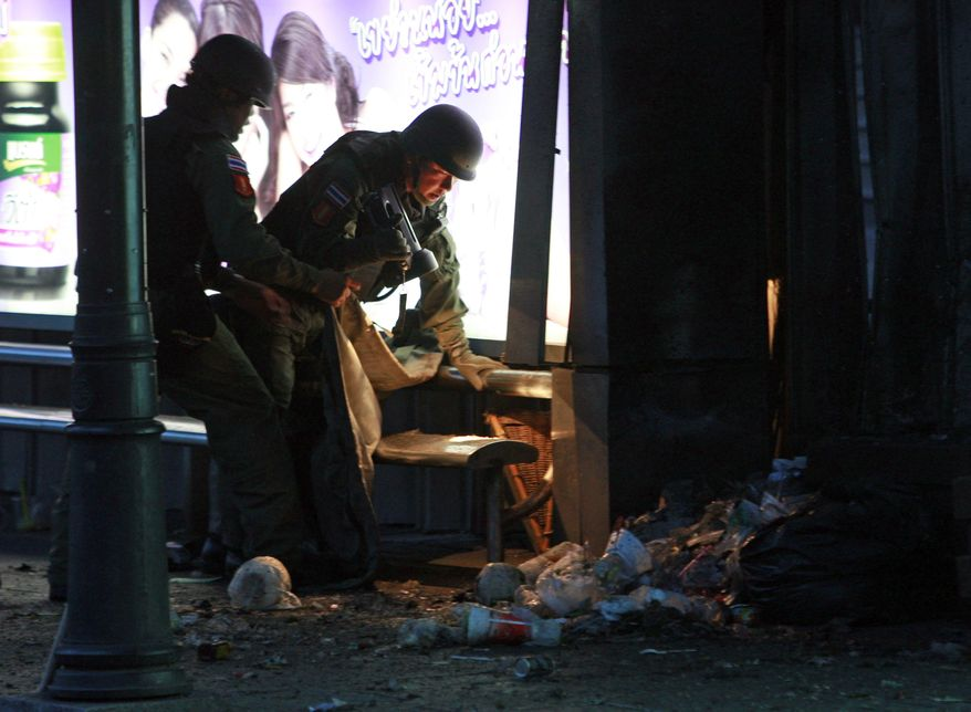 **FILE** Thai bomb squad members examine the site of a bomb blast near a bus stop in downtown Bangkok on July 25, 2010. The bombing wounded nine people shortly after polls closed in a parliamentary election that pitted a government candidate against a jailed leader of recent mass protests in the Thai capital. (Associated Press)
