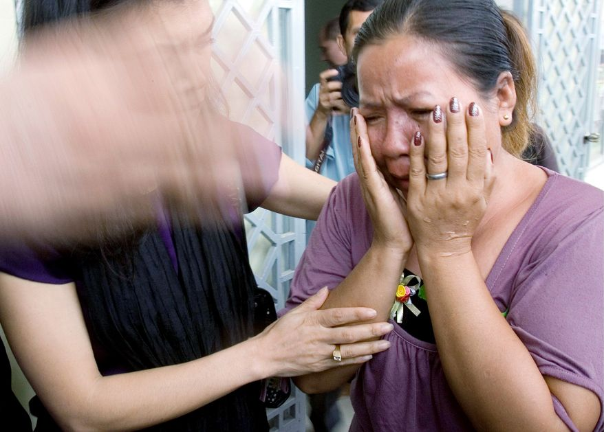 Khmer Rouge victim Hong Savath, 47, weeps Monday in Phnom Penh after the bloody regime's chief jailer, Kaing Guek Eav, was sentenced to 35 years in prison, which likely will keep him jailed just 19 years, for overseeing the deaths of up to 16,000 people. (Associated Press)