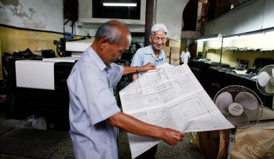 Mr. Chiong (left) checks a newspaper with Guillermo Chiu, an editor in Havana. In a system where the state owns all media, some see the freedoms enjoyed by Havana's Chinese community as a hint at what's to come should communist authorities ever relent. (Associated Press)