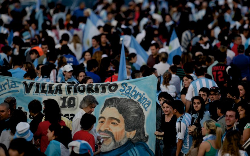 Fans of Argentina's soccer team wait for the players to arrive after their elimination from South Africa 2010 World Cup in Buenos Aires, Sunday, July 4, 2010. The banner shows an image of the team's coach Diego Maradona. (AP Photo/Natacha Pisarenko)