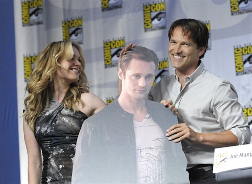 """Actor Stephen Moyer, right, and actress Anna Paquin, left, hold up a cardboard cutout of actor Alexander Skarsgard at a panel discussion of their cable television series """"True Blood"""" at Comic Con in San Diego, Calif. on Friday, July 23, 2010. (AP Photo/Dan Steinberg)"""