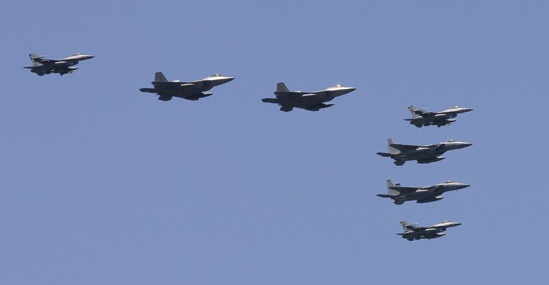 F-22 stealth fighters (second and third from left) fly with other fighters over the Nimitz-class USS George Washington during joint military exercises by the United States and South Korea in the East Sea off the Korean peninsula on Monday, July 26, 2010. (AP Photo/Lee Jin-man, Pool)