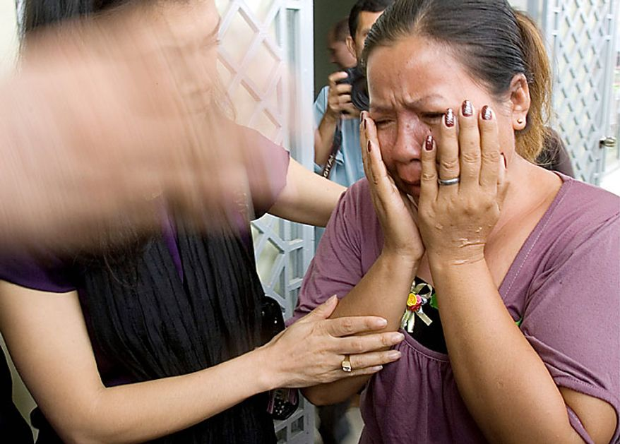Cambodian victim Hong Savath, right, 47, weeps after a verdict was handed down to Kaing Gek Eav, alias Duch, former S-23 prison commander, at the U.N.-backed war crimes tribunal in Phnom Penh, Cambodia, Monday, July 26, 2010. The tribunal sentenced the former Khmer Rouge chief jailer Monday to 35 years in prison, the first verdict involving a leader of the genocidal regime that destroyed a generation of Cambodia's people.  (AP Photo/Heng Sinith)