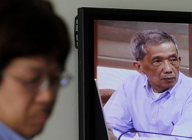 """Kaing Guek Eav, also known as Duch, who ran the notorious Toul Sleng, a top secret detention center for the worst """"enemies"""" of the state, appears on a television screen of the press center of the U.N.-backed war crimes tribunal in Phnom Penh, Cambodia, Monday, July 26, 2010. The tribunal opened Monday to hand down a verdict in the first trial of a senior member of the Khmer Rouge regime that turned Cambodia into a vast killing field three decades ago. (AP Photo/Heng Sinith)"""