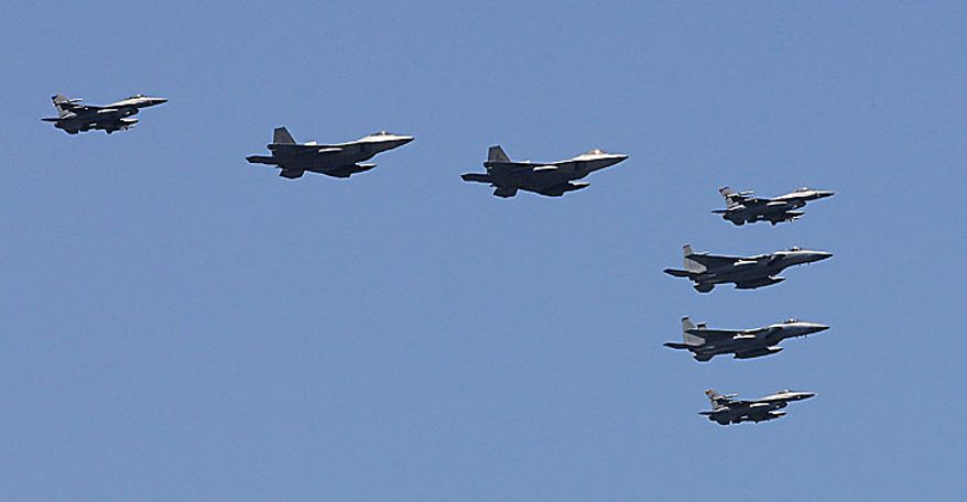 U.S. F-22 stealth fighters, second and third from left, fly with other fighters over the Nimitz-class USS George Washington during joint military exercises between the U.S. and South Korea in South Korea's East Sea on Monday, July 26, 2010. U.S. and South Korean warships and helicopters practiced anti-submarine maneuvers off the Korean Peninsula Monday that officers said they hope would serve as a warning to Pyongyang that aggression in the region would not be tolerated. (AP Photo/ Lee Jin-man, Pool)