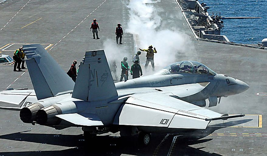 Deck crew members prepare for takeoff of a fighter on the flight deck of the Nimitz-class USS George Washington during joint military exercises between the U.S. and South Korea in South Korea's East Sea on Monday, July 26, 2010. U.S. and South Korean warships and helicopters practiced anti-submarine maneuvers off the Korean Peninsula Monday that officers said they hope would serve as a warning to Pyongyang that aggression in the region would not be tolerated. (AP Photo/ Lee Jin-man, Pool)