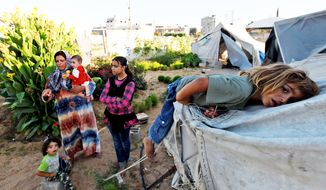 Palestinian Wafa Awaja (holding baby) stands outside the makeshift structures that house her, her husband and their six children — including (from the left) Zikrayat, 2, infant Leyali, Omsyat, 13, and Dia, 4 — in Beit Lahiya, Gaza Strip. (Associated Press)