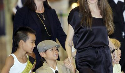 """U.S. actress Angelina Jolie, second from right, and her children from left, 8-year-old Maddox, Zahara Marley, 6, in a yellow shirt hidden behind Maddox, Pax Thien, 6, and Shiloh Nouvel, 4, arrive at Narita International Airport in Narita near Tokyo Monday, July 26, 2010 for the Japan premiere of her spy action-thriller film """"Salt."""" (AP Photo/Koji Sasahara)"""