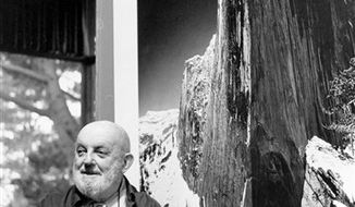 "FILE - In this Dec. 2,1980 file photo showing late photographer, Ansel Adams posing in front of his photograph of one the views of Yosemite National Park titled ""Monolith:  The Face of Half Dome, 1927,"" in his home in Carmel Highlands, Calif.  A lawyer says a trove of old glass negatives found in Fresno have been authenticated as the work of iconic photographer Ansel Adams and are worth at least $200 million. The negatives were bought 10 years ago at a garage sale in Fresno for $45. (AP Photo/Paul Sakuma,File)"
