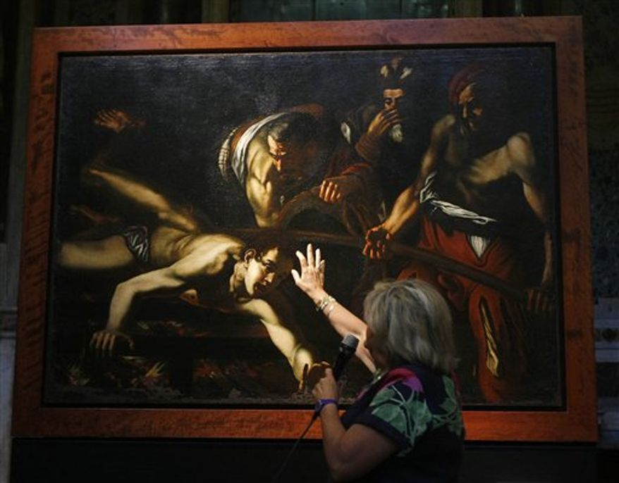 "Art superintendent Rossella Vodret illustrates some detail of the painting at the center of the latest Caravaggio mystery, after the Vatican newspaper first suggested and then denied that the canvas was the work of the Italian master, in Rome, Italy, Tuesday, July 27, 2010. The ""Martyrdom of St. Lawrence"" would now be examined to ascertain its attribution, but Vodret and other Caravaggio scholars attending the unveiling agreed the painting did not look like a Caravaggio, but rather like the work of his followers. They said the quality did not hold up to Caravaggio's standards. (AP Photo/Pier Paolo Cito)"