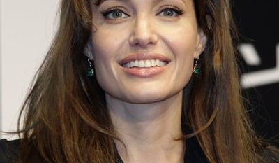 """U.S. actress Angelina Jolie, right, and Sony Corp. Chief Executive Howard Stringer pose during the Japan premiere of her spy action-thriller film """"Salt"""" in Tokyo,  Tuesday, July 27, 2010. (AP Photo/Shizuo Kambayashi)"""