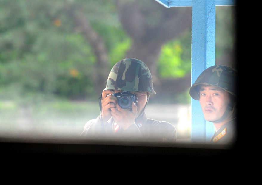 A North Korean soldier takes pictures of the southern side of the cross-border village of Panmunjom on Tuesday, July 27, 2010. Both Koreas and the United States on Tuesday marked the 57th anniversary of the signing of the Korean War armistice against the backdrop of U.S.-South Korean military drills. (AP Photo/Kim Jae-hwan, Pool)