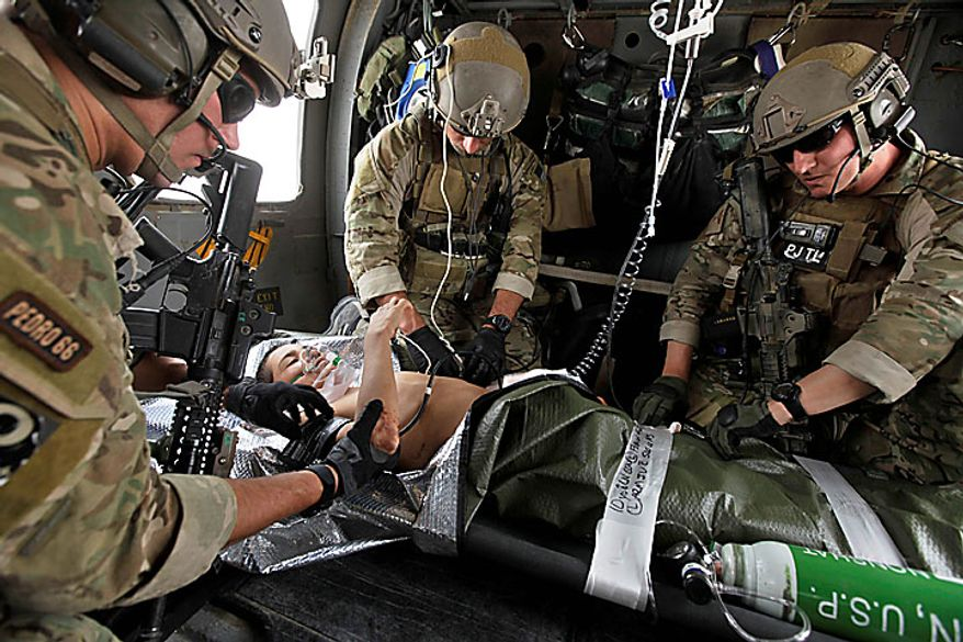 "Pararescuemen, or ""PJs,"" of the 58th Rescue Squadron deployed to Afghanistan from Nellis Air Force Base, Las Vegas, left to right, Senior Airman Robert Dieguez, 1st Lt. Matthew Carlisle, and Tech. Sgt. Jeff Hedglin, stabilize an Afghan boy with a gunshot wound to the torso, aboard a Pavehawk CASEVAC helicopter en route to a nearby military hospital in Kandahar province, Tuesday July 27, 2010.  The PJs and helicopter aircrews are part of the U.S. Air Force's 451st Air Expeditionary Wing based at Kandahar Air Field, which provides a variety of air assets to the NATO war effort in southern Afghanistan. (AP Photo/Brennan Linsley)"