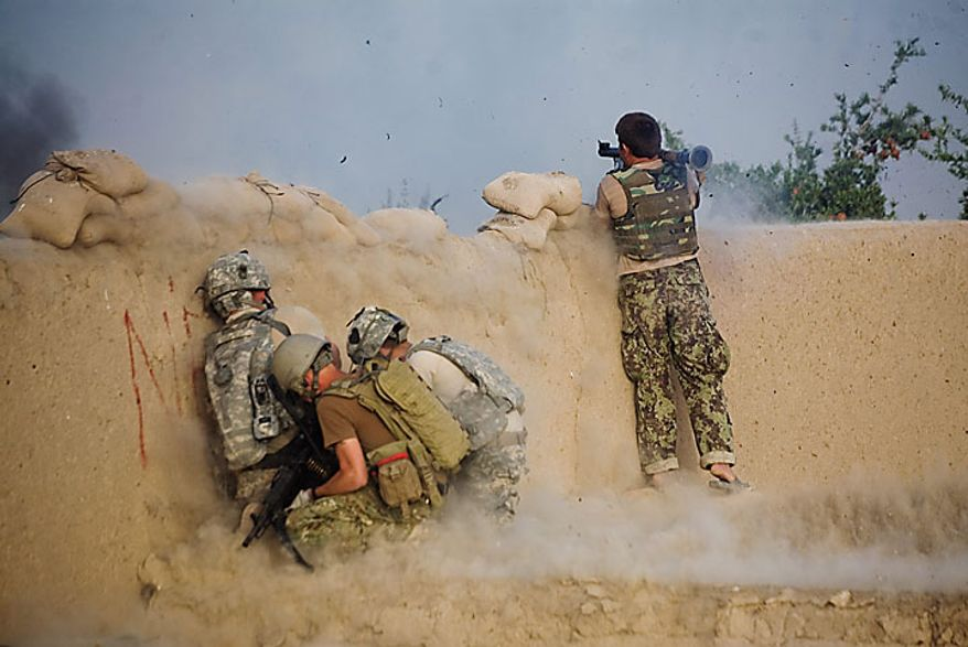 An Afghan soldier launches a rocket propelled grenade as US soldiers of the 1-320th Alpha Battery, 2nd Brigade of the 101st Airborne Division duck during a clash with insurgents at COP Nolen, in the volatile Arghandab Valley, Kandahar, Afghanistan, Tuesday, July 27, 2010. (AP Photo/Rodrigo Abd)