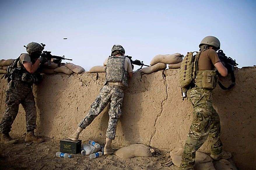 US soldiers from 1-320th Alpha Battery, 2nd Brigade of the 101st Airborne Division, fire towards insurgents after coming under attack by Taliban at COP Nolen, in the volatile Arghandab Valley, Kandahar, Afghanistan, Tuesday, July 27, 2010. (AP Photo/Rodrigo Abd)