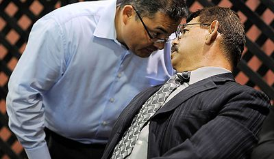 Pedro Carrillo, left, interim city manager of Bell, Calif., shares a word with city councilor George Mirabal during a city council meeting addressing city leaders' pay, Monday, July 26, 2010, in Bell, Calif. (AP Photo/Chris Pizzello)
