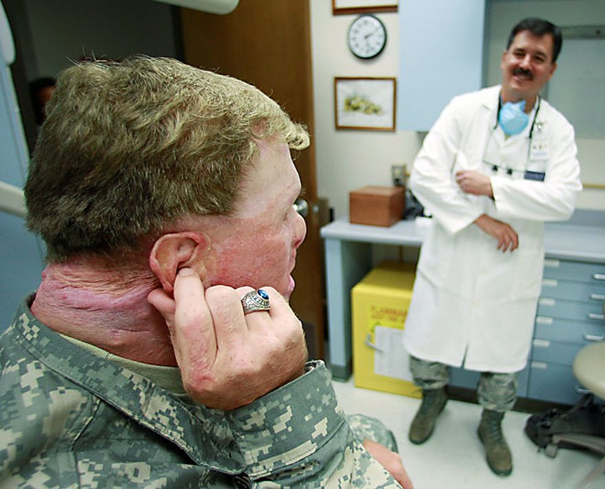 In this photo taken June 23, 2010, Master Sgt. Todd Nelson, left, visits with Dr. Joe Villalobos, right, during a visit to makes adjustments to a prosthetics ear at Wilford Hall Medical Center in San Antonio. Nelson was injured in 2007 by an explosion while serving in Afghanistan. (AP Photo/Eric Gay)