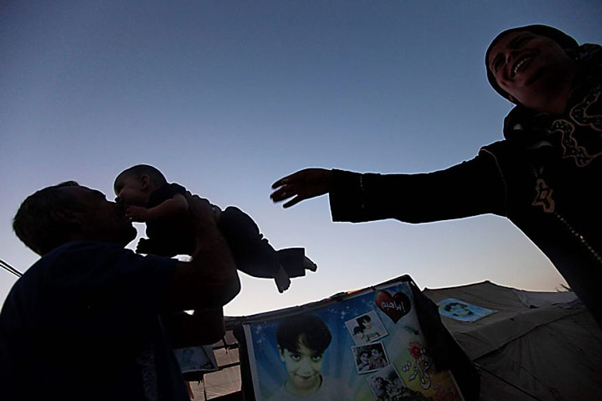 Palestinian Kamal Awaja, left, plays with his five month-old daughter Leyali, as his wife, Wafa gestures outside the makeshift structures that house the family, in Beit Lahiya, northern Gaza Strip, Wednesday June 16, 2010. The Awajas are among thousands of families whose houses were destroyed during Israel's three-week military offensive against Hamas-ruled Gaza, launched in December 2008 with the aim of halting Hamas rocket attacks. An Israeli forces bulldozer flattened the Awajas' house and as the family tried to flee, bullets hit Kamal, Wafa, and their 8-year-old son Ibrahim, who bled to death in the street. Ibrahim's picture decorates the tent bottom center. (AP Photo/Lefteris Pitarakis)