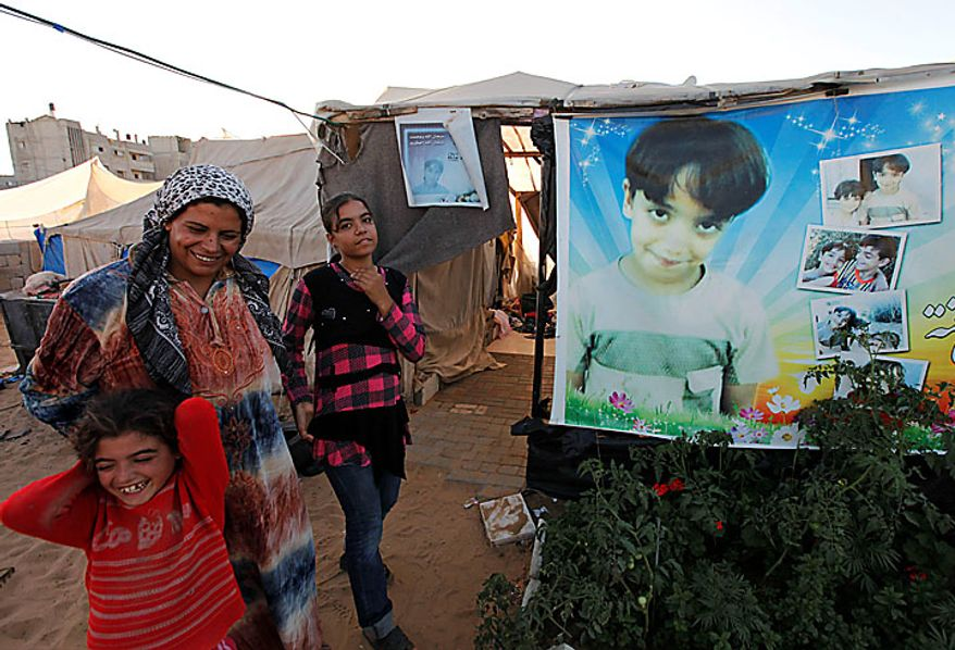 Palestinian Wafa Awaja, 34, jokes with her daughters Hala, 8, left, and Omsyat, 13, as they stand near the makeshift structures that house the family in Beit Lahiya, northern Gaza Strip, Thursday, June 10, 2010. A portrait of Wafa's late 8-year-old son Ibrahim _ killed during an Israeli army operation_ is attached to the tent at right. The Awajas are among thousands of families whose houses were destroyed during Israel's three-week military offensive against Hamas-ruled Gaza, launched in December 2008 with the aim of halting Hamas rocket attacks. An Israeli forces bulldozer flattened the Awajas' house and as the family tried to flee, bullets hit Wafa, her husband Kamal, and Ibrahim, who bled to death in the street. (AP Photo/Lefteris Pitarakis)