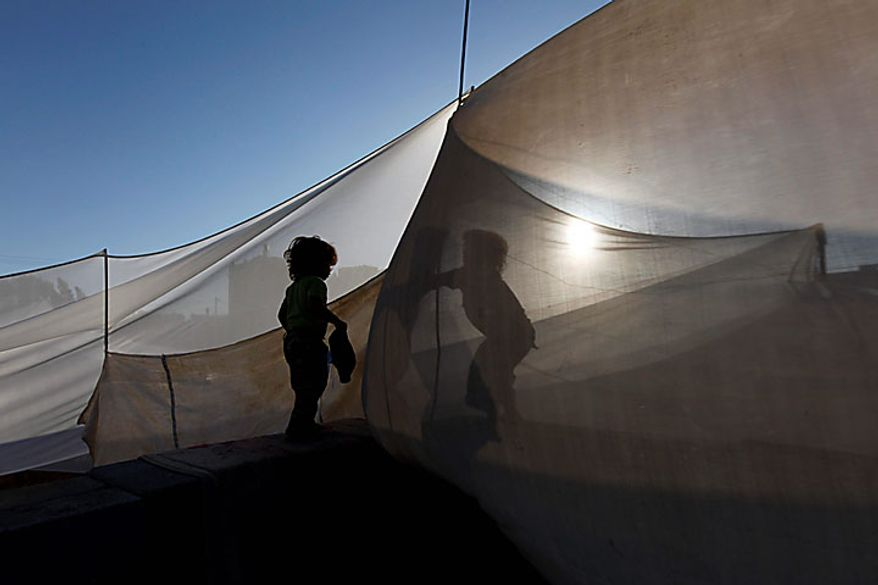 Palestinian siblings Dia Awaja, right, 4, and Zikrayat, 2, left, play on one of the tents which comprise the makeshift structures that house their family, in Beit Lahiya, northern Gaza Strip, Thursday, June 10, 2010. The Awajas are among thousands of families whose houses were destroyed during Israel's three-week military offensive against Hamas-ruled Gaza, launched in December 2008 with the aim of halting Hamas rocket attacks. An Israeli forces bulldozer flattened the Awajas' house and as the family tried to flee, bullets the siblings father Kamal, mother Wafa, and their 8-year-old brother Ibrahim, who bled to death in the street. (AP Photo/Lefteris Pitarakis)
