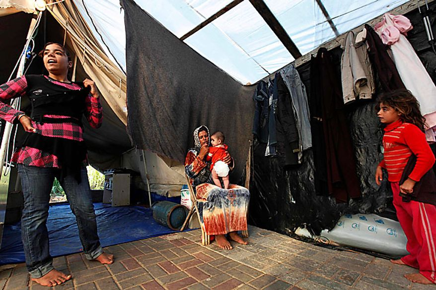 Members of the Awaja family, from left: Omsyat, 13, mother Wafa, 34,  five month-old Leyali, and Hala, 8, are seen in a makeshift structure that houses them in Beit Lahiya, northern Gaza Strip, June 10, 2010. The Awajas are among thousands of families whose houses were destroyed during Israel's three-week military offensive against Hamas-ruled Gaza, launched in December 2008 with the aim of halting Hamas rocket attacks. An Israeli forces bulldozer flattened the Awajas' house and as the family tried to flee, bullets hit father Kamal, Wafa, and their 8-year-old son Ibrahim, who bled to death in the street. (AP Photo/Lefteris Pitarakis)