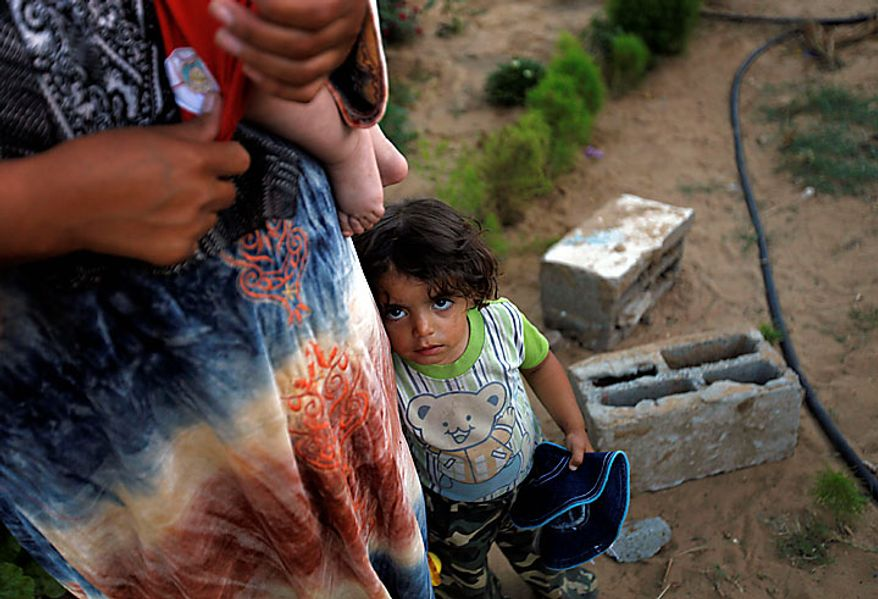 Palestinian Wafa Zikrayat, 2, stands next to her mother Wafa, 34, holding baby Leyali, near the makeshift structures that house the family in Beit Lahiya, northern Gaza Strip, Thursday, June 10, 2010. The Awajas are among thousands of families whose houses were destroyed during Israel's three-week military offensive against Hamas-ruled Gaza, launched in December 2008 with the aim of halting Hamas rocket attacks. An Israeli forces bulldozer flattened the Awajas' house and as the family tried to flee, bullets hit father Kamal, his wife Wafa, and their 8-year-old son Ibrahim, who bled to death in the street. (AP Photo/Lefteris Pitarakis)