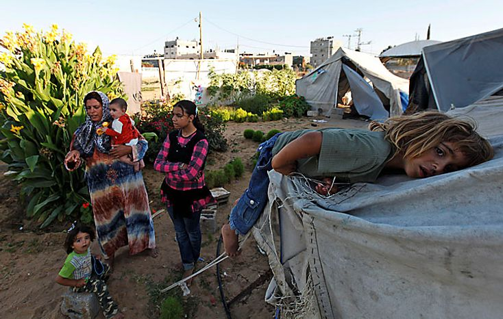 Members of the Palestinian Awaja family, from left, Zikrayat, 2, mother Wafa, 34, holding baby Leyali, Omsyat, 13, and Dia, 4, on tent, stand near the makeshift structures that house them in Beit Lahiyeh, northern Gaza Strip, Thursday, June 10, 2010. The Awajas are among thousands of families whose houses were destroyed during Israel's three-week military offensive against Hamas-ruled Gaza, launched in December 2008 with the aim of halting Hamas rocket attacks. An Israeli forces bulldozer flattened the Awajas' house and as the family tried to flee, bullets hit father Kamal, Wafa, and their 8-year-old son Ibrahim, who bled to death in the street. (AP Photo/Lefteris Pitarakis)