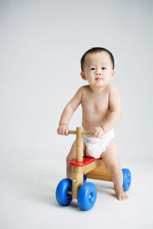 Baby on toy bike (OJO Images via AP Images)