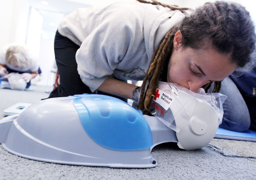 "Jessica Kocian practices first-aid response for CPR during a Red Cross course in Chicago in May 2008. Two new studies conclude that ""hands only"" chest compression is enough to save a life in many cases, even without mouth-to-mouth resuscitation. (Associated Press)"