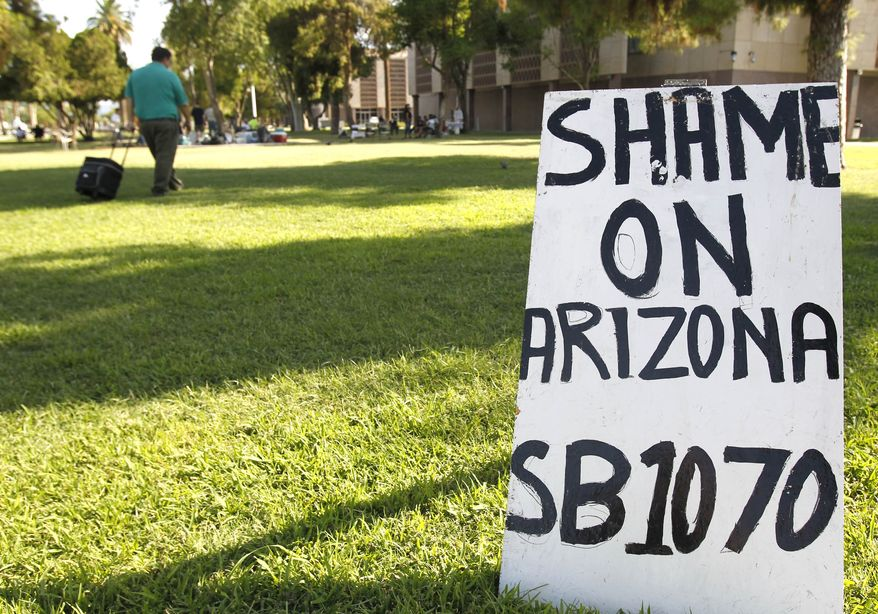 Signs set up by opponents of the new Arizona immigration law SB1070 dot the grounds at the Arizona capitol Monday, July 26, 2010, in Phoenix. A federal judge blocked key sections of the law Wednesday, July 28, 2010, hours before it was to take effect. (AP Photo/Ross D. Franklin)