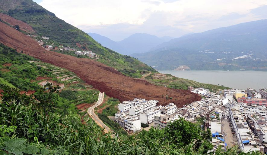 A landslide sweeps aside buildings in the village of Wangong in Hanyuan county in Ya'an in southwest China's Sichuan province in this Tuesday, July 27, 2010, file photo. (AP Photo) ** FILE **