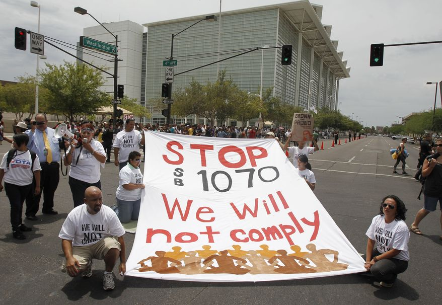 In an act of civil disobedience protesters block the street to protest the SB1070 Arizona immigration law in front of U.S. District Court Thursday, July 22, 2010, in Phoenix. U.S. District Judge Susan Bolton, on Wednesday, July 28, 2010, blocked sections of a new Arizona immigration law from taking effect July 29. (AP Photo/Ross D. Franklin)