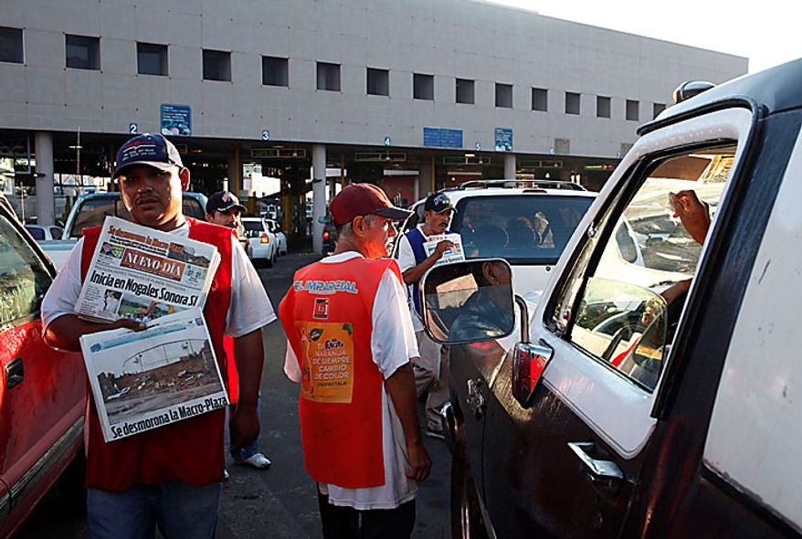 Vendors sell newspapers at the Nogales Port of Entry in Nogales, Sonora, Mexico, Wednesday, July 28, 2010. Arizona's new immigration law SB1070 takes effect Thursday, July 29. (AP Photo/Jae C. Hong)