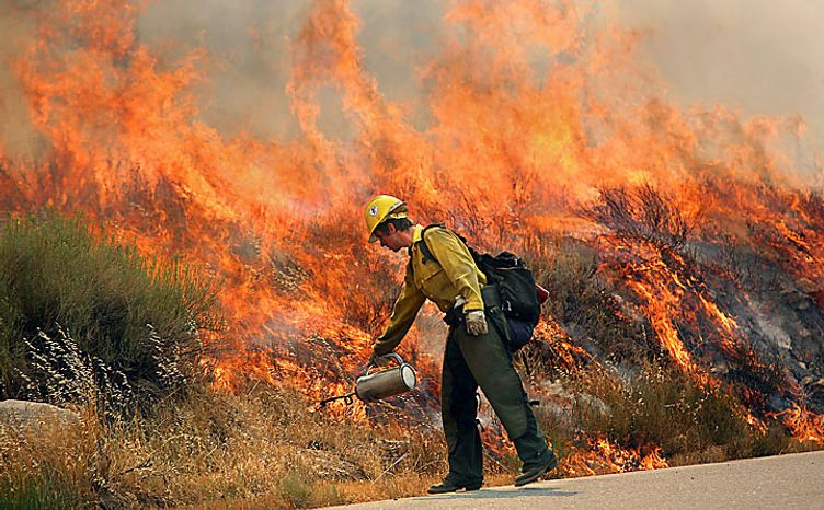 U.S. Forest Service firefighter, Brant Machado, with the Fulton Hotshots, lights a backburn along Sierra Highway, near Riverkern, Calif., Tuesday, July 27, 2010. A fire in Sequoia National Forest has destroyed six homes, charred eight square miles and forced the evacuation of 122 juvenile offenders attending a forestry camp near the California town of Kernville. (AP Photo/The Bakersfield Californian, Casey Christie)