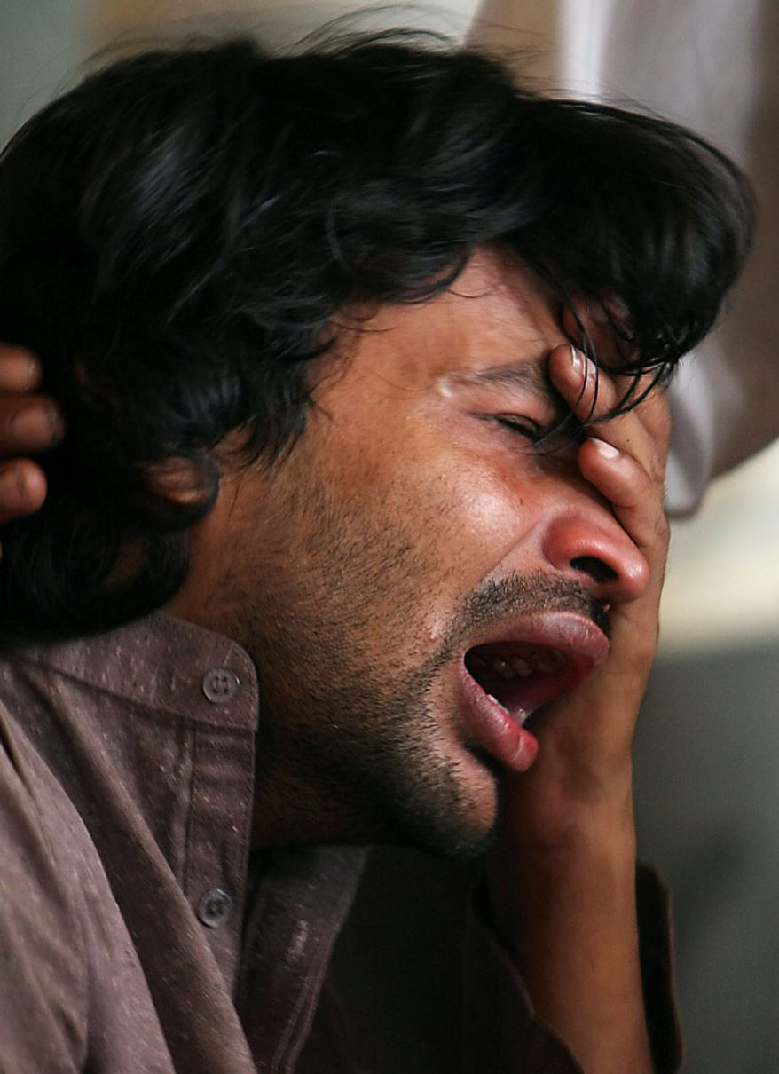 A Pakistani man mourns the death of his family member who was killed in a plane crash at Karachi airport in Pakistan on Wednesday, July 28, 2010. The passenger jet carrying 152 people crashed into the hills surrounding Pakistan's capital amid poor weather Wednesday, officials said. (AP Photo/Fareed Khan)