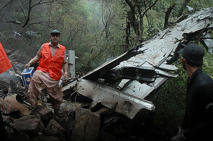 Pakistani rescue workers examine the site of a plane crash in Islamabad, Pakistan on Wednesday, July 28, 2010. The passenger jet carrying 152 people crashed Wednesday into the hills surrounding Pakistan's capital amid poor weather, killing dozens of people and stoking fears nobody could have survived the disaster. (AP Photo)