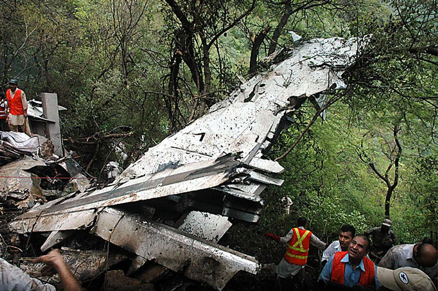 Pakistani rescuers surround the wreckage of a plane that crashed in Islamabad, Pakistan on Wednesday, July 28, 2010. A government official says all 152 people on board the plane that crashed in the hills surrounding Pakistan's capital were killed. (AP Photo)