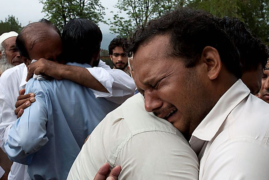 Relatives mourn the deaths of their family members killed in a plane crash, outside a local hospital in Islamabad, Pakistan on Wednesday, July 28, 2010. The passenger jet carrying 152 people crashed into the hills surrounding Pakistan's capital amid poor weather Wednesday, officials said. (AP Photo/Naveed Ali)