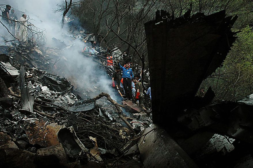 Pakistani rescue workers examine the site of a plane crash in Islamabad, Pakistan on Wednesday, July 28, 2010.  A government official said all 152 people on board the plane that crashed in the hills surrounding Pakistan's capital were killed. (AP Photo)