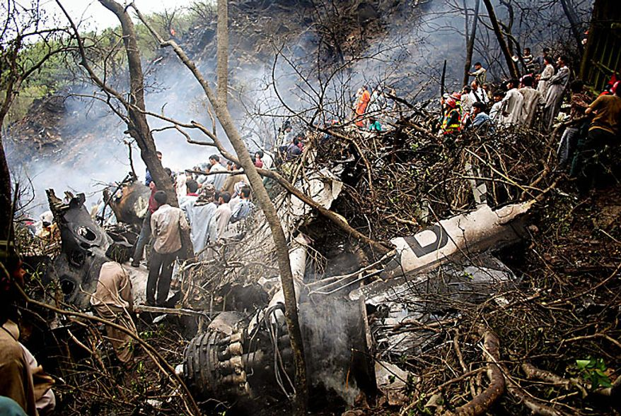 Pakistani rescuers surround the wreckage of a plane that crashed in Islamabad, Pakistan on Wednesday, July 28, 2010. The passenger jet carrying 152 people on board crashed into the hills surrounding Pakistan's capital amid poor weather Wednesday, officials said. (AP Photo/Irfan Haider)