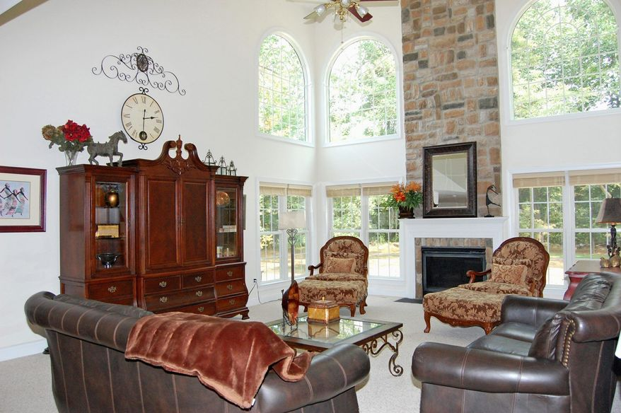 The floor-to-ceiling stone fireplace, surrounded by windows, is the focal point of the two-story family room. The room features easy access to the kitchen and backyard.