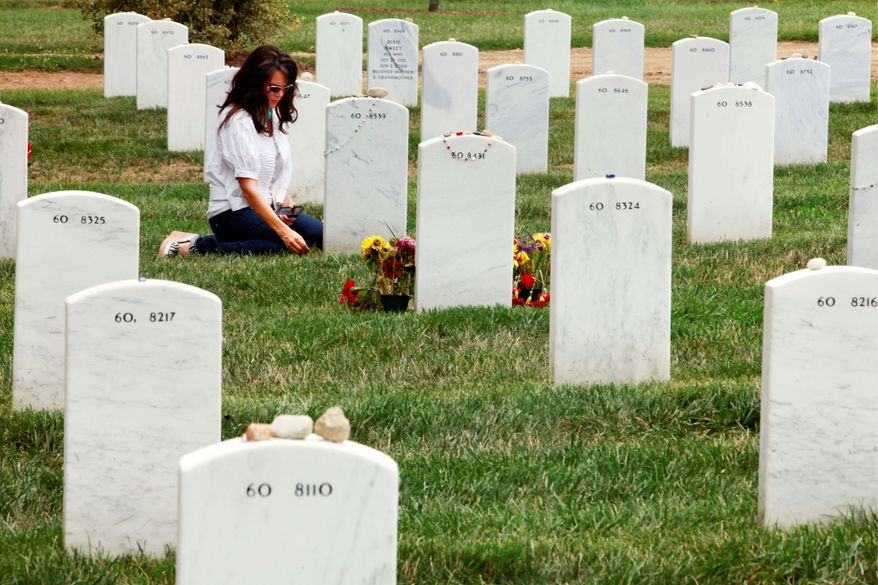 Associated Press A woman visits a grave in Section 60, where many soldiers from the Iraq and Afghanistan wars are buried, at Arlington National Cemetery in Arlington, Va. The number of graves that might be affected by mix-ups at Arlington National Cemetery grew from hundreds to as many as 6,600 on Thursday.