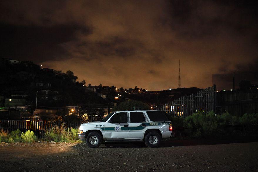 ** FILE ** A U.S. Border Patrol vehicle sits along the U.S.-Mexico border in Nogales, Ariz., on Tuesday, July 27, 2010. (AP Photo/Jae C. Hong, File)