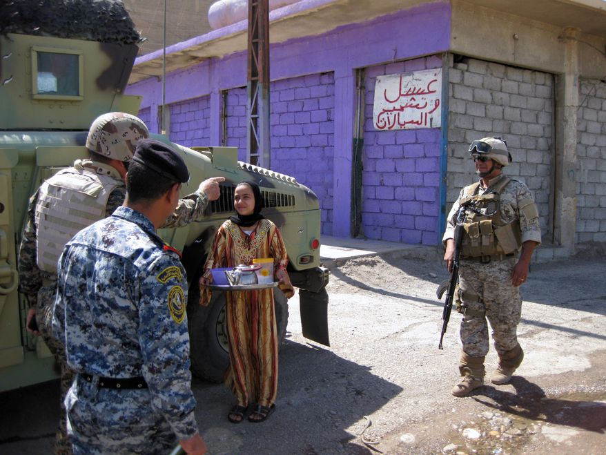 A girl offers tea to Iraqi army soldiers and a federal police commander as they begin a search for bomb makers in a warehouse district in western Mosul, 225 miles northwest of Baghdad, on Wednesday, July 28, 2010. (AP Photo/Lara Jakes)