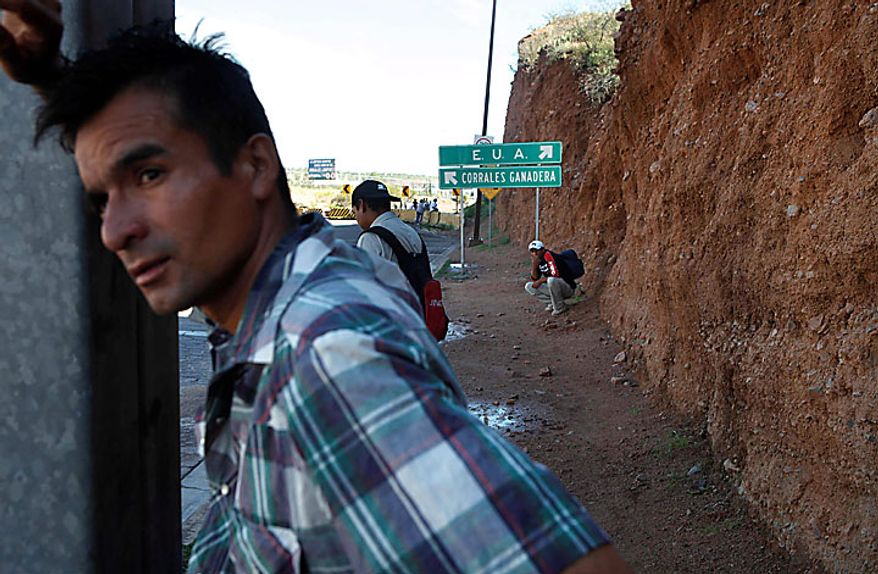 **FILE** With a sign indicating the direction to the United States at top center, deportees stand near the U.S.-Mexico border in Nogales, Sonora, Mexico, on July 29, 2010. (Associated Press)