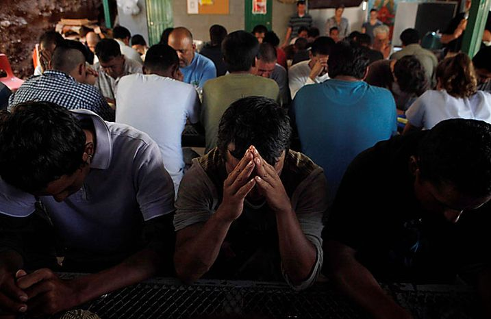 Deportees pray as they gather for breakfast provided by the Kino Border Initiative in Nogales, Sonora, Mexico, Thursday, July 29, 2010. Opponents of Arizona's immigration crackdown went ahead with protests Thursday despite a judge's ruling that delayed enforcement of most the law. (AP Photo/Jae C. Hong)