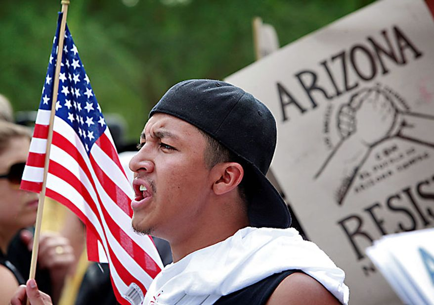 Julio Fierro Jr., 19, of Tucson, protests Thursday, July 29, 2010 in Phoenix to rally against Arizona's new immigration law, SB1070. Opponents of Arizona's immigration crackdown went ahead with protests Thursday despite a judge's ruling that delayed enforcement of most the law. (AP Photo/Matt York)