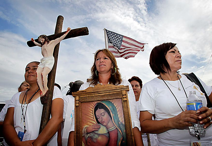 From left, Maria Duran, Maria Uribe and Giornia Sanchez march in protest Thursday, July 29, 2010 in Phoenix to rally against Arizona's new immigration law, SB1070. Opponents of Arizona's immigration crackdown went ahead with protests Thursday despite a judge's ruling that delayed enforcement of most the law. (AP Photo/Matt York)