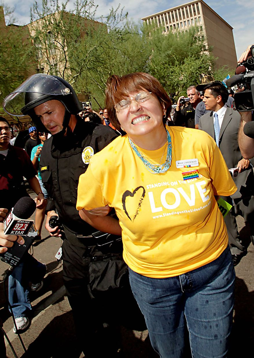 A protester is arrested Thursday, July 29, 2010 in Phoenix while rallying against Arizona's new immigration law, SB1070. Opponents of Arizona's immigration crackdown went ahead with protests Thursday despite a judge's ruling that delayed enforcement of most the law. (AP Photo/Matt York)